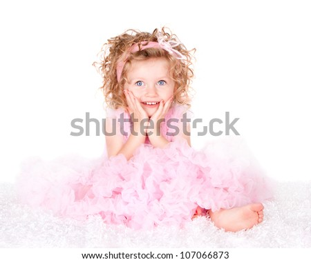 A toddler with blue eyes and curly hair with a surprised look on her face