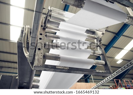 A toilet paper making machine producing toilet and bathroom paper rolls. Paper and tissue manufacturers factory and engineered machinery. Mass produced bathroom products.