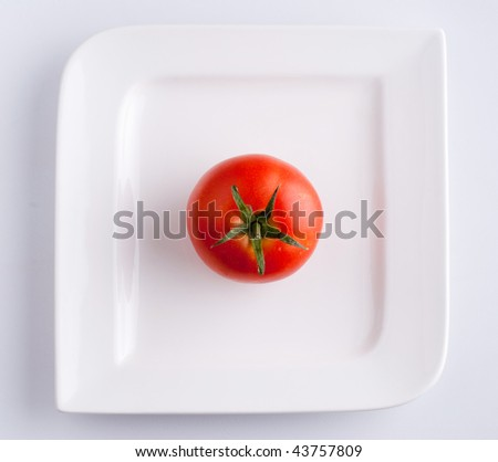 A tomato on a white plate - top view