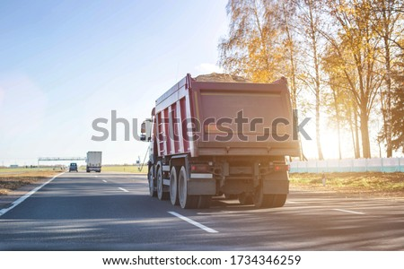 A 40 ton truck carries construction sand on the highway. Concept of overload on the roads and rental of a dump truck for work, copy space