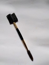 a tool made of plastic, the tip of which has a small comb and a small brush, as a tool for makeup on eyebrows or eyelashes