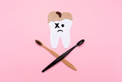 A tooth cut out of felt, affected by caries, with crossed toothbrushes, in the form of a skull and bones. Flat lay. Pink background. The concept of dental diseases.