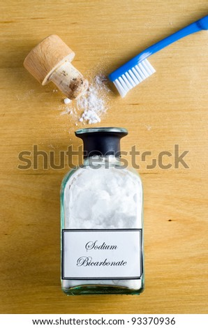 A toothbrush and a  bottle of Sodium Bicarbonate (baking soda) laid flat and shot from overhead on a wooden table.  Cork open and powder spilling on to table.