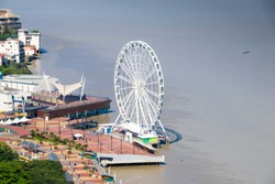 A top aerial view of Guayaquil city in Ecuador. Buildings, Malecon 2000, La Perla ferris wheel and the Guayas river.
