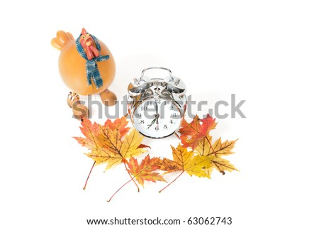 A top close-up view studio shot of a silver alarm clock with a plastic hen and fall leaves. - stock photo
