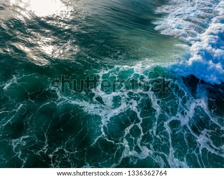 A top down drone image where the waves break, before and after. Leaving in the swirl the white foam and deep greens as well as the surface wave breaks. Taken just off Burleigh Heads.