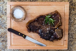 A top-down shot of a cooked T-bone steak topped with rosemary, thyme, and kosher salt on a cutting board next to a steak knife and a small wooden bowl of kosher salt.