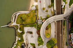A top-down shot over a curved roadway, which is the entrance and exit for Waterfront Park in Dobbs Ferry, NY. It looks like the breast cancer ribbon. It is a cloudy morning and the park is empty.