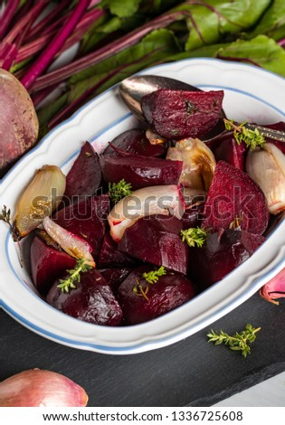 A top down view of a serving dish of beets and shallots surrounded by raw beets and shallots.