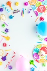 A top down view of birthday party items arranged in a border frame.