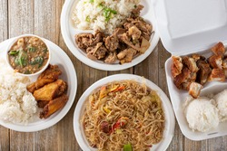 A top down view of several Filipino entrees on a wood surface.