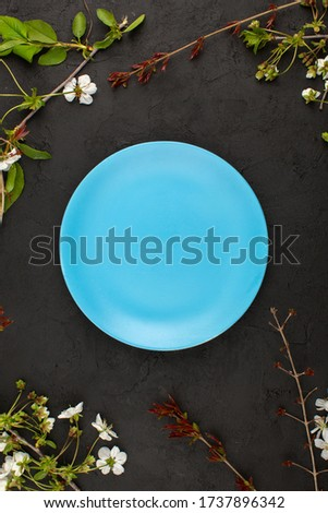 a top view blue plate empty around white flowers on the dark background