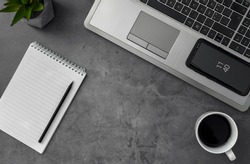 A top view grayscale shot of a laptop, mobile phone, coffee, and notebook on a table