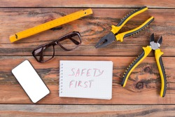 A top view image of various hand tools consist of pliers, nippers, ruler. Safety first written on notepad in the center.