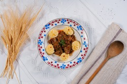 A top view of a beef dish with dumplings on a white tablecloth with a wooden spoon and wheat sheaves