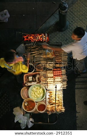 A top view of a sidewalk food stand in Bangkok at night