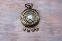 A top view of a vintage pocket watch and tiles spelling out 'love