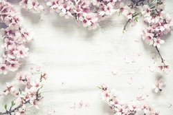 A top view of a White wood textured background decorated with almond rose flowers
