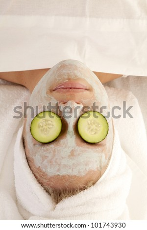 A top view of a woman in the spa with cucumbers on her eyes.