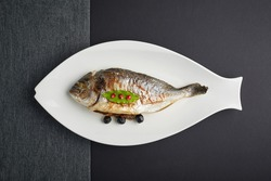 a top view of baked filled dorado served on a white herring-dish in the grey background