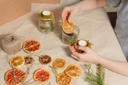 A top view of childrens hands making candles of pine cones in glass can are on kraft beige paper background with dry slices of gold orange, grapefruits, green pine branch, candles. Handmade