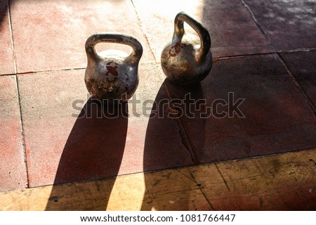 A top view of couple of steel kettlebells on a blurred background. A kettlebell on a gym floor. Workout. Copy space. Training crossfit and healthy lifestyle concept