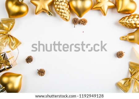 A top view of golden christmas ornaments positioned as a frame on white background #1192949128