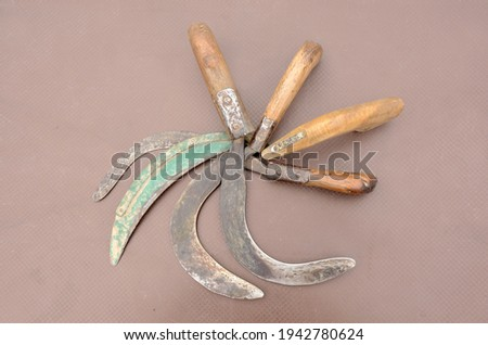 A top view of old rusty sharp sickles with wooden handles on the brown surface Foto stock ©
