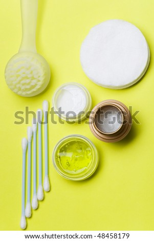 A top view of the items for personal care arrange in a light green background. Swabs and cotton pads for face, cream, lip balm, gel and pilling brush.