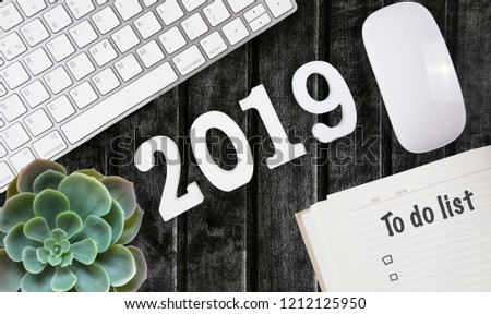 A top view of the workspace with a mouse and keyboard on the dark wooden background. phrases on stickers. Plans, goals , results of the year 2019, to do list. Happy New Year's layout. Flatlay #1212125950