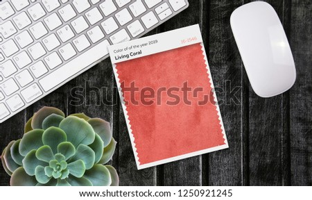 A top view of the workspace with a mouse and keyboard on the dark wooden background. phrases on stickers. Color of the year 2019 Living coral #1250921245