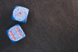 A top view of two blue dice on a black surface