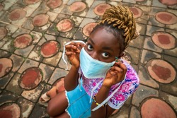 A top wide angle view of a beautiful young black girl wearing a surgical mask for protection - concept black on how to wear a mask in covid-19 season.