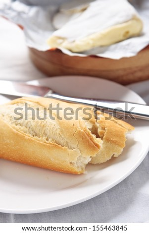 A torn piece of baguette with french brie
