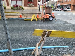 A torn up street with a makeshift water pipe on the side. There are yellow barriers along the way to stop pedestrians from disturbing the ongoing roadwork and public service repairs.