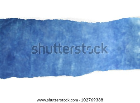 A Torn white paper reveals blue background.