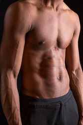 A torso of an Afro-American athletic young man with a perfect 6 pack abs isolated on the black background
