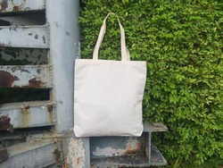 A tote bag hanging on a tree background.