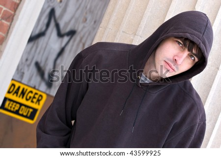 A tough looking guy posing in a grungy urban setting in a hooded sweat shirt.