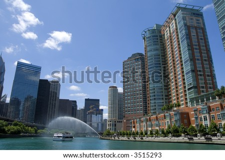 A tour boat waits near a fountain beneath new condominiums on the Chicago River.
