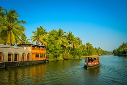A tourist boat passes through a traditional Kerala houseboat on the backwater of Vembanad Lake