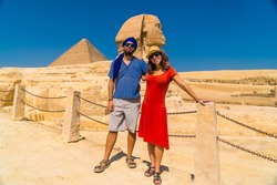 A tourist couple at The Great Sphinx of Giza and in the background the Pyramids of Giza, the oldest Funerary monument in the world. In the city of Cairo, Egypt