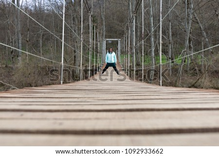 A tourist girl is standing on a suspension bridge. Suspension bridge over the river. #1092933662