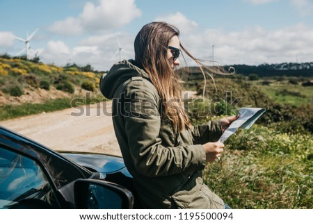 A tourist girl next to the car looks at the map of the area for further travel.