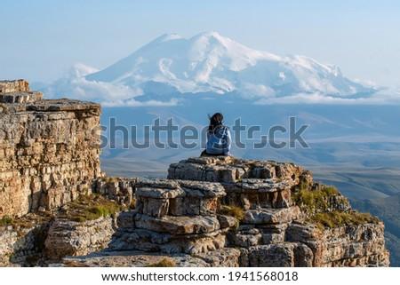 A tourist (girl) sits on the cliff edge of Bermamyt plateau against mount Elbrus. Karachay-Cherkessia, Caucasus, Russia.