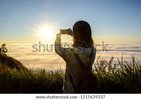 A tourist girl take a picture of the sunrise in the morning at the mountain, Phu chi fa in Chiangrai,Thailand