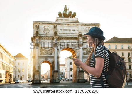 A tourist girl with a backpack looks sights in Munich in Germany. Passes by the triumphal arch. #1170578290