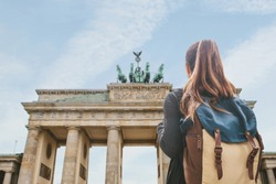 A tourist girl with a backpack or student looking at the Brandenburg Gate in Berlin in Germany.