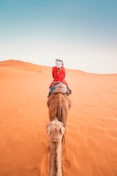 A tourist girl with a traditional moroccan red dress riding a dromedary in the Sahara desert of Merzouga, Morocco