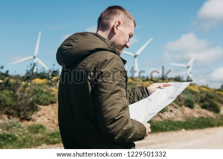 A tourist man looks at the map of the area for further travel. Unknown terrain or unfamiliar territory or path.